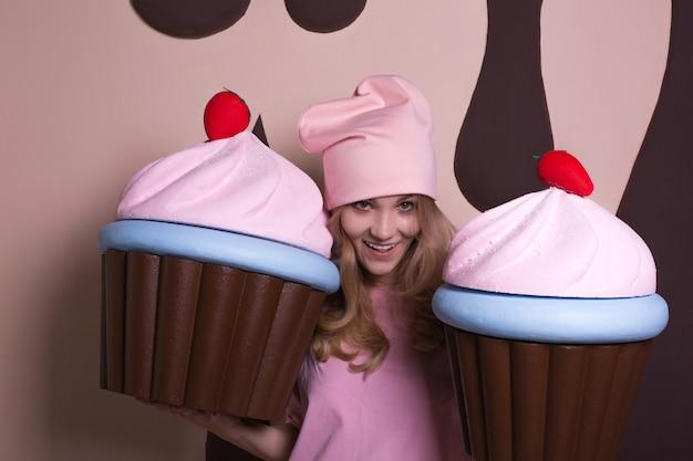 Zalotna blondynka w różowej czapce, ciesząca się dużymi babeczkami w studio