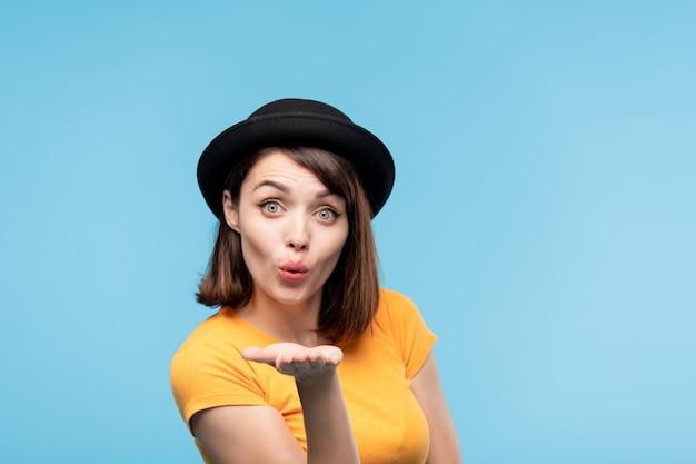 Zalotna brunetka w czarnym kapeluszu, wysyła ci pocałunek, trzymając rękę przed sobą w izolacji