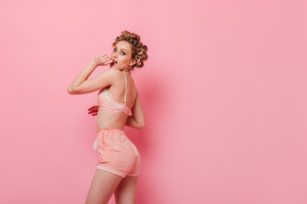 Zalotna dama z lokami ubrana w różową piżamę pozuje na odizolowanej ścianie