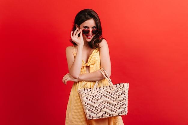 Zalotna dziewczyna w letnim stroju uśmiecha się słodko, zdejmując stylowe okulary przeciwsłoneczne. portret młodej kobiety z ciemnymi kręconymi włosami na czerwonej ścianie.