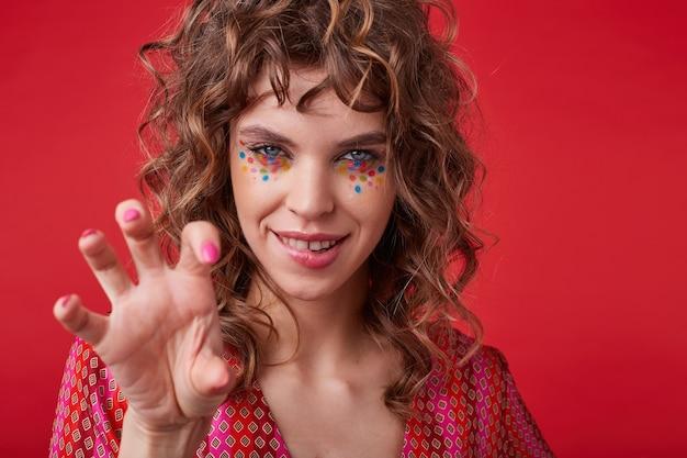 Zalotna młoda, kręcona kobieta z wielobarwnymi kropkami na twarzy, która szuka i gryzie dolną wargę, żartobliwie podnosząc rękę