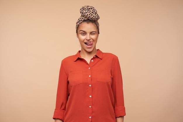 Zalotna młoda ładna brązowowłosa kobieta radośnie mrugająca z przodu i wystawiająca język, stojąc na beżowej ścianie w zwykłym ubraniu