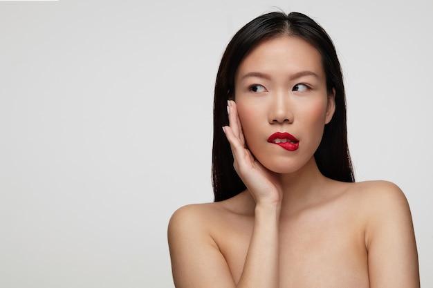 Zalotna młoda piękna brunetka kobieta z przypadkową fryzurą dotykającą jej twarzy uniesioną ręką i patrzącą na bok zalotna, odizolowana na białej ścianie