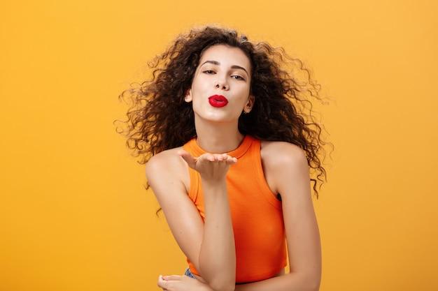 Zalotna pewna siebie i zmysłowa stylowa kobieta z kręconą fryzurą i czerwoną szminką składającą usta trzyma...