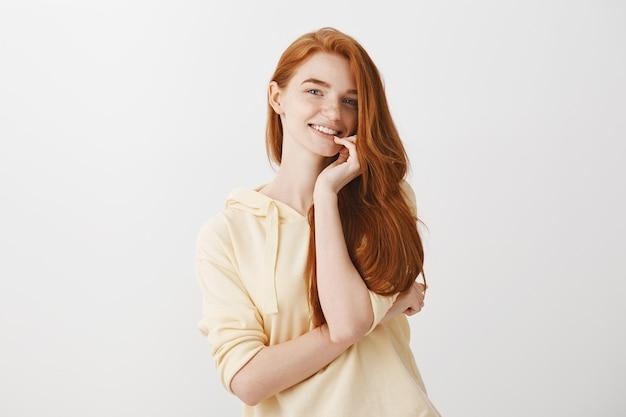 Zalotna wspaniała ruda kobieta uśmiechnięta zachwycona