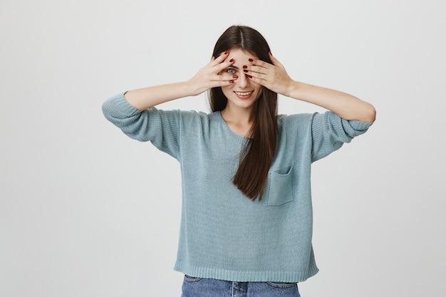 Zalotnie uśmiechnięta kobieta zasłania oczy i zerka przez palce