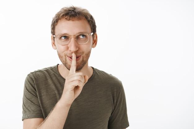 Zalotny i niegrzeczny facet mający intrygujący sekret, mówi cii z palcem wskazującym na ustach
