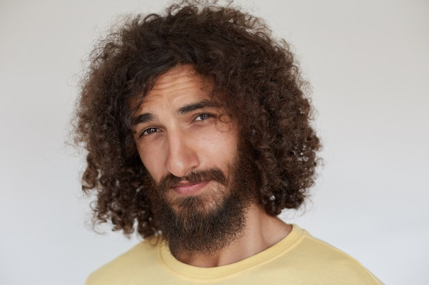 Zalotny, młody, kręcony brunet z brodą wyglądający figlarnie z założonymi ustami, mrużący i mrużący czoło, ubrany w zwykłe ubrania