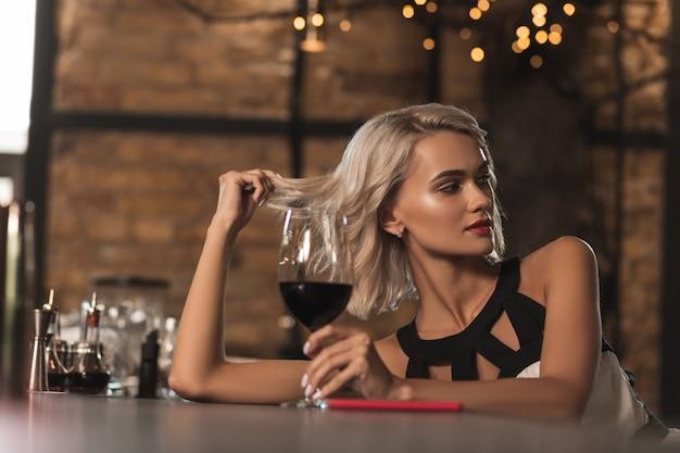 Zalotny nastrój. atrakcyjna blondynka siedzi przy barze, pije wino i flirtuje z kimś po drugiej stronie baru
