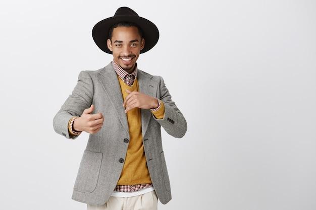 Zalotny, romantyczny mężczyzna, który chce się bawić. zadowolony pewny siebie afroamerykanin w stylowym czarnym kapeluszu i kurtce, wykonujący zmysłowe i namiętne gesty, uśmiechający się ciekawie nad szarą ścianą