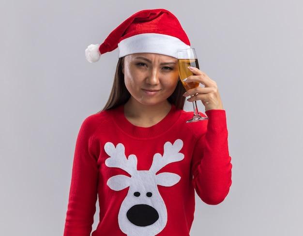 Żałowana młoda azjatycka dziewczyna ubrana w świąteczny kapelusz ze swetrem trzymając kieliszek szampana na czole na białym tle