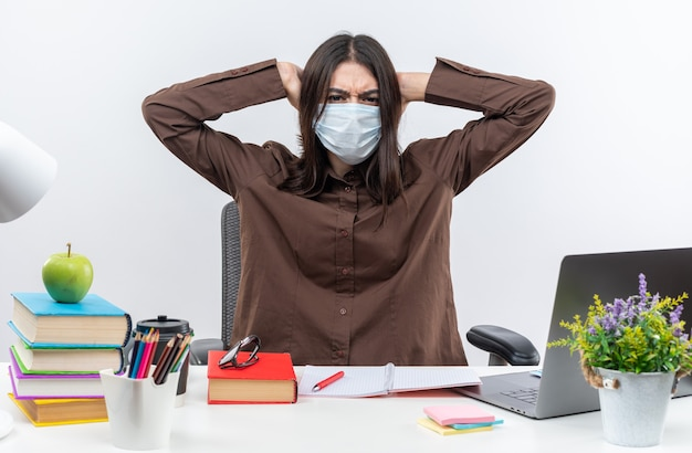 Żałowana młoda szkolna kobieta w masce medycznej siedzi przy stole z szkolnymi narzędziami chwyconymi za głowę
