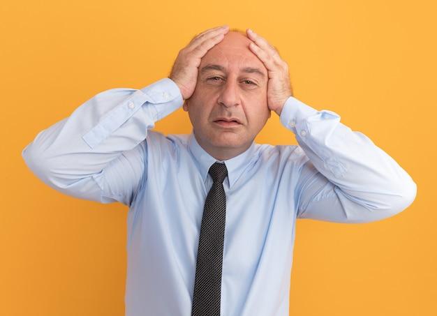 Żałowany mężczyzna w średnim wieku ubrany w białą koszulkę z krawatem złapał głowę na białym tle na pomarańczowej ścianie