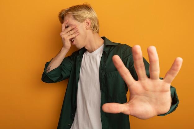 Żałowany młody blondyn ubrany w zielony t-shirt zakrył twarz ręką i wyciągnął rękę