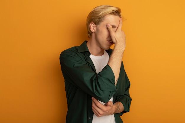 Żałowany młody blondyn ubrany w zielony t-shirt zakrył twarz ręką