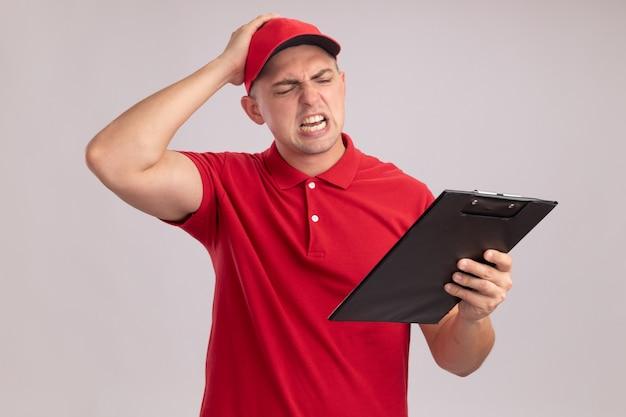 Żałowany młody człowiek dostawy ubrany w mundur z czapką trzymając i patrząc na schowek kładąc rękę na głowie na białym tle na białej ścianie