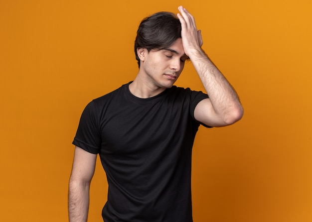 Żałowany młody przystojny facet ubrany w czarną koszulkę kładąc rękę na czole na białym tle na pomarańczowej ścianie