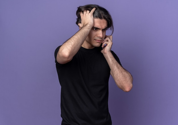 Żałowany młody przystojny facet ubrany w czarną koszulkę rozmawia przez telefon i chwycił głowę odizolowaną na fioletowej ścianie