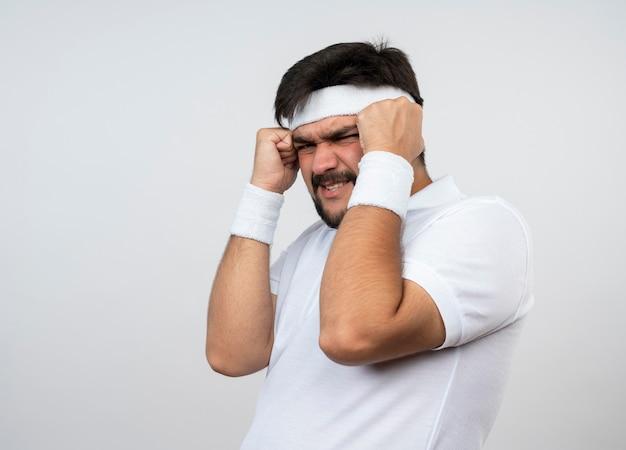 Żałowany młody sportowiec w opasce i opasce kładzie ręce na głowie na białym tle na białej ścianie z miejsca na kopię
