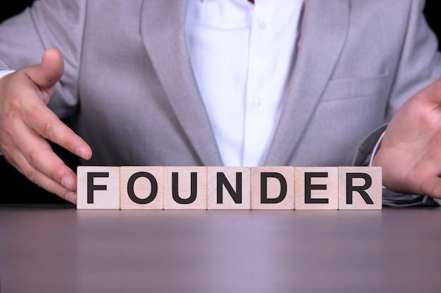 Założyciel, słowo zapisane na drewnianych kostkach, na tle biznesmen w szarym garniturze.