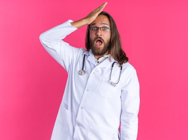 Żałując dorosły mężczyzna lekarz ubrany w szatę medyczną i stetoskop w okularach patrząc na kamerę trzymając rękę na głowie odizolowaną na różowej ścianie