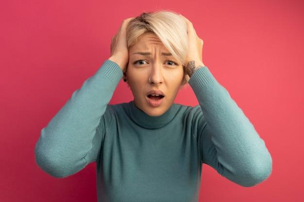Żałując, młoda blondynka kładzie ręce na głowie, wyglądając na odizolowaną na różowej ścianie