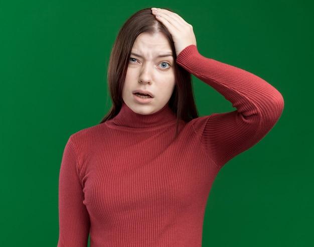 Żałując, młoda ładna kobieta kładzie rękę na głowie