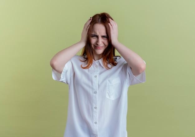 Żałując, młoda ruda dziewczyna złapała głowę na białym tle na oliwkowozielonej ścianie