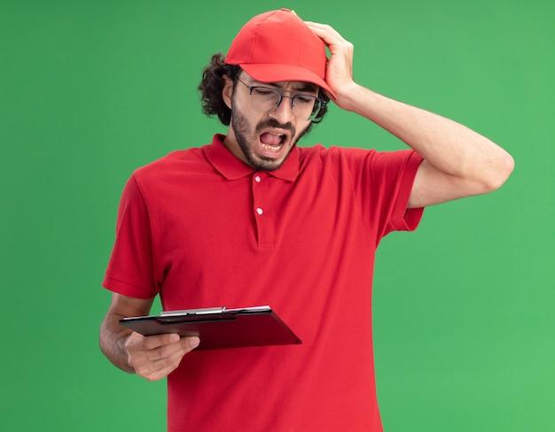 Żałując młody człowiek dostawy w czerwonym mundurze i czapce w okularach, trzymając schowek i ołówek, kładąc rękę na głowie, patrząc na schowek na białym tle na zielonej ścianie