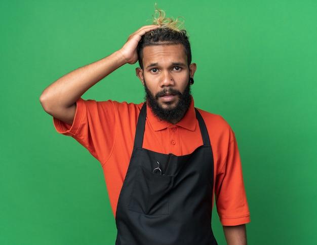 Żałując, młody męski fryzjer ubrany w mundur, patrząc na przód, kładąc rękę na głowie, odizolowany na zielonej ścianie