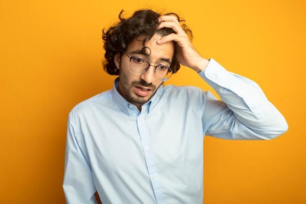 Żałując, młody przystojny kaukaski mężczyzna w okularach kładąc rękę na głowie patrząc w dół na białym tle na pomarańczowym tle