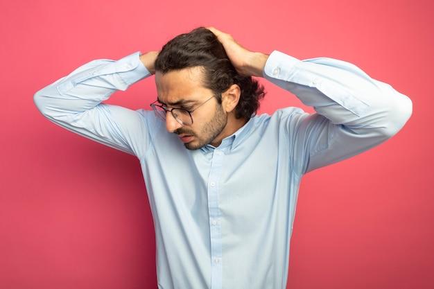 Żałując, młody przystojny mężczyzna w okularach, trzymając ręce na głowie, patrząc w dół na białym tle na różowej ścianie