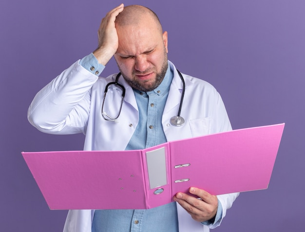 Żałując, że lekarz w średnim wieku ma na sobie szatę medyczną i stetoskop, trzymając rękę na głowie, trzymając otwarty folder, patrząc na niego na fioletowej ścianie