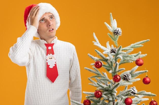Żałując, że młody przystojny facet w świątecznym kapeluszu i krawacie świętego mikołaja stoi w pobliżu udekorowanej choinki, kładąc rękę na głowie patrząc w górę na pomarańczowej ścianie