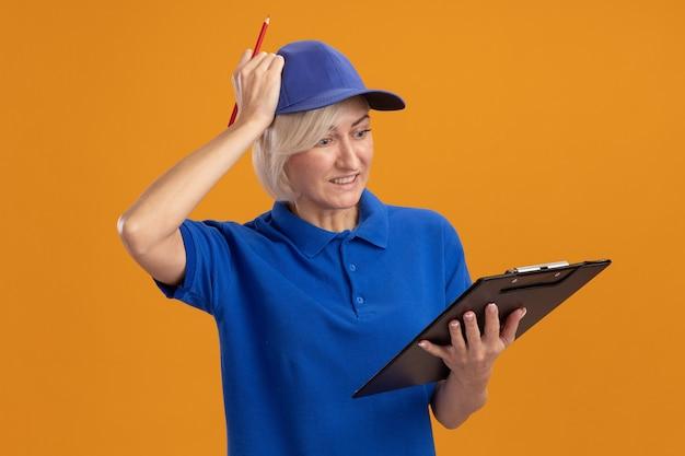Żałująca blondynka w średnim wieku dostarczająca kobieta w niebieskim mundurze i czapce trzymająca schowek i ołówek patrząca na schowek kładąca dłoń na głowie na białym tle na pomarańczowym tle