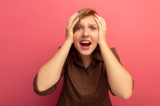 Żałująca młoda blondynka trzymająca ręce na głowie, wyglądająca na odizolowaną na różowej ścianie