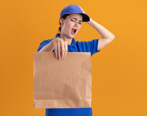 Żałująca młoda kobieta dostarczająca w mundurze i czapce wyciągająca papierową paczkę, patrząc na nią, kładąc rękę na głowie odizolowaną na pomarańczowej ścianie