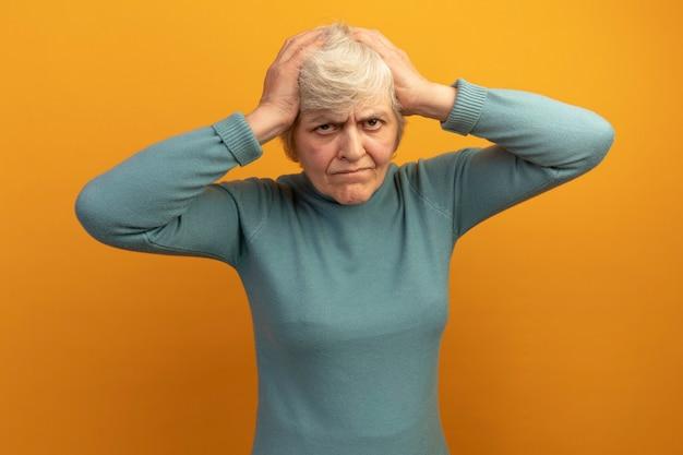 Żałująca stara kobieta ubrana w niebieski sweter z golfem, patrząca z przodu, kładąca ręce na głowie odizolowana na pomarańczowej ścianie