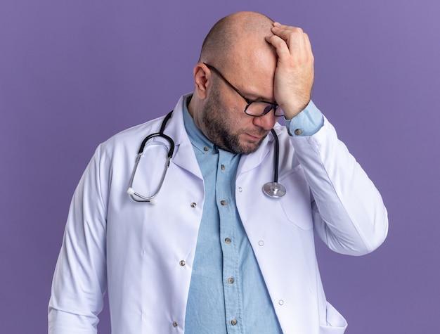 Żałujący lekarz w średnim wieku ubrany w szatę medyczną i stetoskop w okularach trzymających rękę na głowie z zamkniętymi oczami