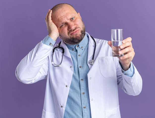 Żałujący mężczyzna w średnim wieku, ubrany w szatę medyczną i stetoskop, trzymający szklankę wody, trzymający rękę na głowie, patrząc na przód odizolowany na fioletowej ścianie