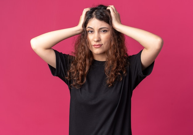 Żałuję, młoda ładna kobieta patrząca na przód trzymająca ręce na głowie odizolowana na szkarłatnej ścianie