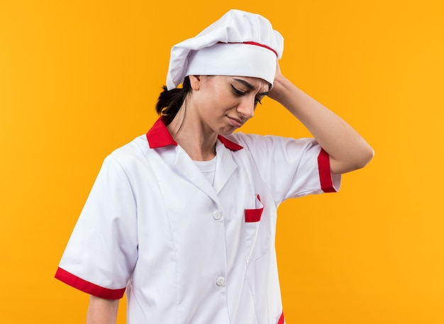 Żałuję, Patrząc W Dół, Młoda Piękna Dziewczyna W Mundurze Szefa Kuchni, Kładąc Rękę Na Głowie Premium Zdjęcia