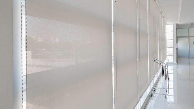 Żaluzje poziome na szklanym oknie wnętrz, żaluzje do salonu dekoracja okienna w celu ochrony domu przed światłem słonecznym, zasłona przeciwsłoneczna w biurze