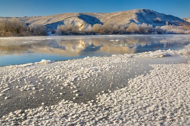 Zamarzająca rzeka z pagórkowatych brzegów i wielkich kry lodowych
