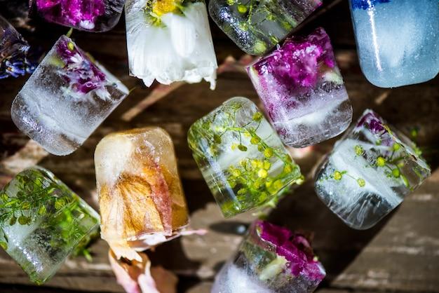 Zamarznięci kwiaty w kostkach lodu na nieociosanym drewnianym tle