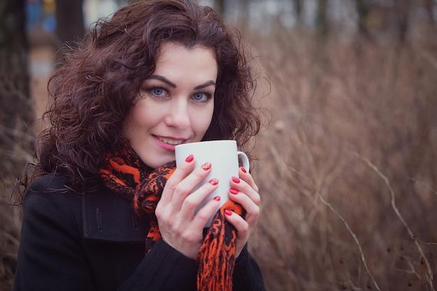 Zamarznięta kobieta pije swój gorący napój, herbatę lub kawę z filiżanki.