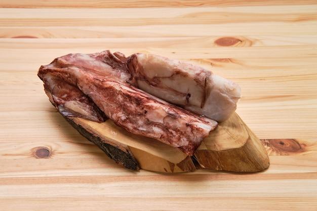 Zamarznięta świeża ośmiornica lub kałamarnicy surowi na drewnianej desce
