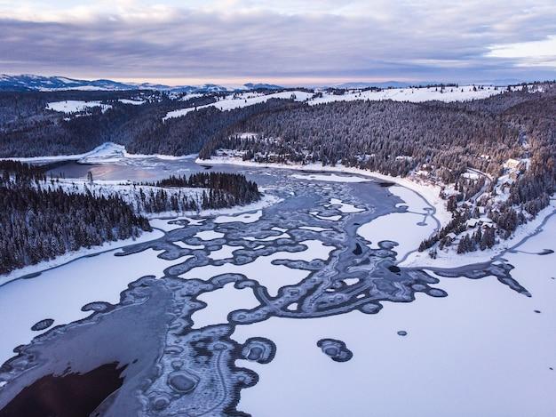 Zamarznięte jezioro z górami i lasami pokrytymi śniegiem w transylwanii w rumunii