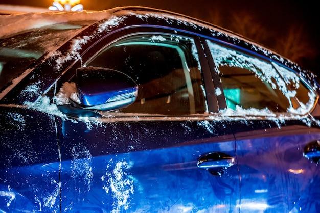 Zamarznięte lusterko wsteczne i wycieraczka samochodu z soplem, lodem i szronem