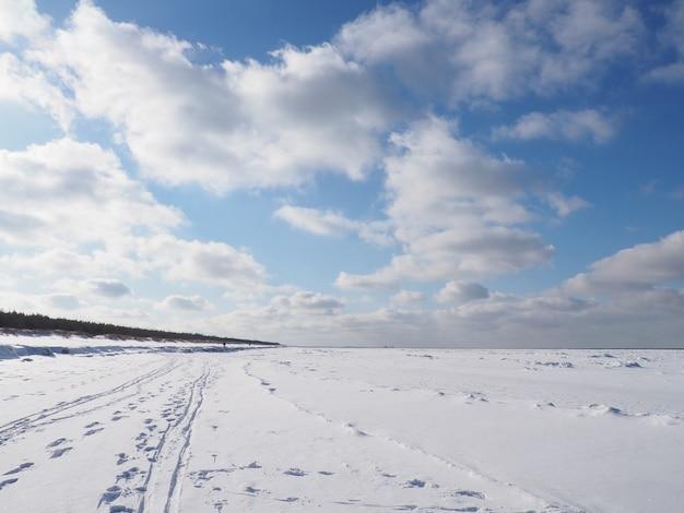 Zamarznięte morze z linią brzegową ze śniegiem i chmurami na niebie w słoneczny dzień
